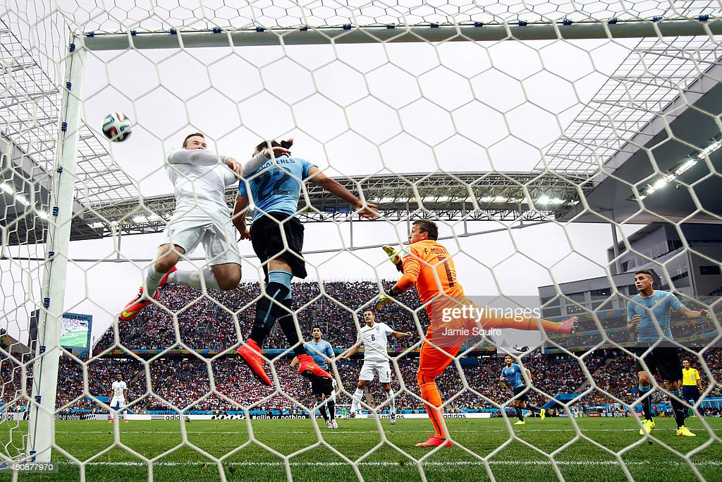 Wayne Rooney of England hits the crossbar with a header against Martin Caceres and goalkeeper Fernando Muslera of Uruguay during the 2014 FIFA World...