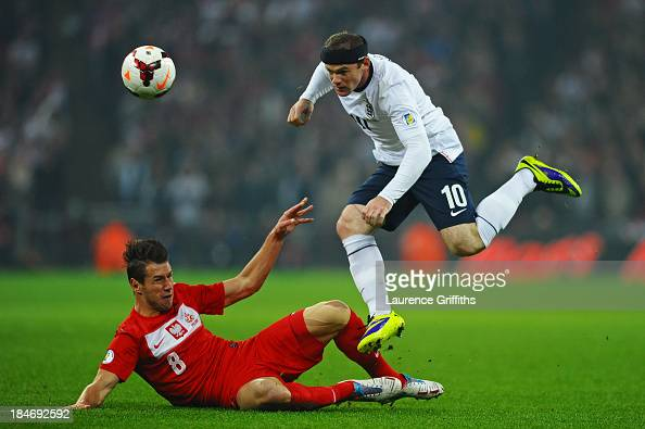 Wayne Rooney of England hurdles the challenge from Grzegorz Krychowiak of Poland during the FIFA 2014 World Cup Qualifying Group H match between...