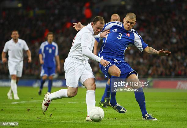 Wayne Rooney of England is challenged by Martin Skrtel of Slovakia during the International Friendly match between England and Slovakia at Wembley...