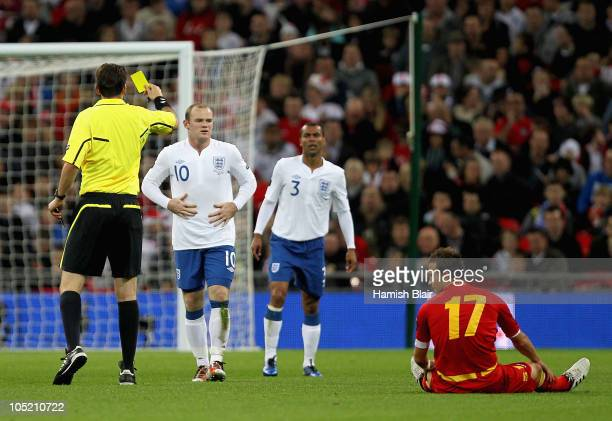 Wayne Rooney of England is shown the yellow card by Referee Manuel Grafe during the UEFA EURO 2012 Group G Qualifying match between England and...