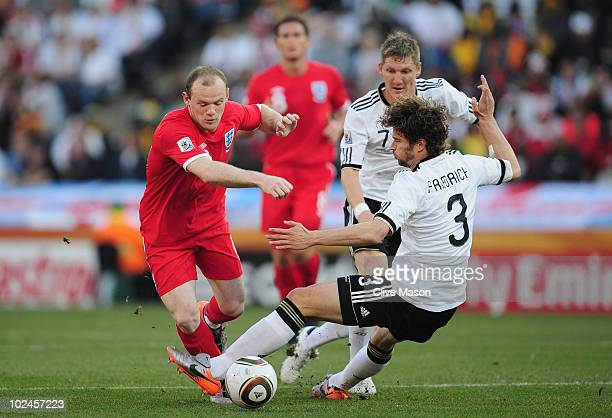 Wayne Rooney of England is tackled by Arne Friedrich of Germany during the 2010 FIFA World Cup South Africa Round of Sixteen match between Germany...