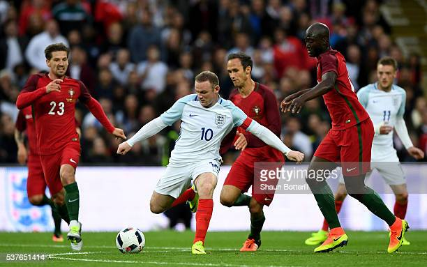Wayne Rooney of England is watched by Adrien Silva Ricardo Carvalho and Danilo Pereira of Portugal during the international friendly match between...