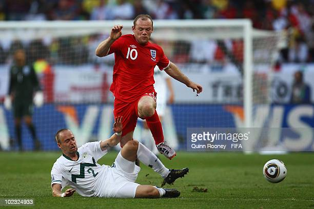 Wayne Rooney of England jumps over Miso Brecko of Slovenia during the 2010 FIFA World Cup South Africa Group C match between Slovenia and England at...