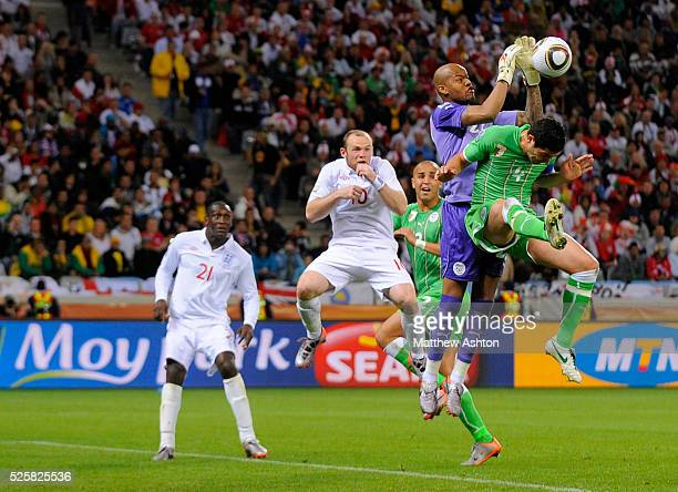 Wayne Rooney of England looks on as goalkeeper Rais M Bolhi of Algeria saves the ball