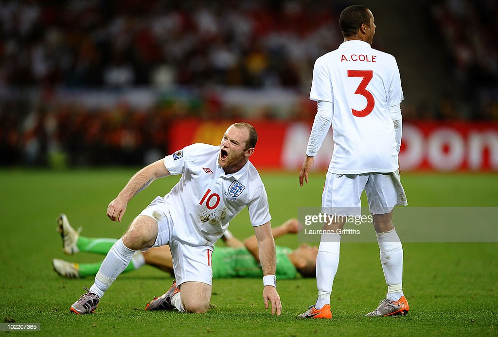 <a gi-track='captionPersonalityLinkClicked' href=/galleries/search?phrase=Wayne+Rooney&family=editorial&specificpeople=157598 ng-click='$event.stopPropagation()'>Wayne Rooney</a> of England reacts after he tackles <a gi-track='captionPersonalityLinkClicked' href=/galleries/search?phrase=Karim+Matmour&family=editorial&specificpeople=741965 ng-click='$event.stopPropagation()'>Karim Matmour</a> of Algeria as <a gi-track='captionPersonalityLinkClicked' href=/galleries/search?phrase=Ashley+Cole&family=editorial&specificpeople=201831 ng-click='$event.stopPropagation()'>Ashley Cole</a> looks on during the 2010 FIFA World Cup South Africa Group C match between England and Algeria at Green Point Stadium on June 18, 2010 in Cape Town, South Africa.