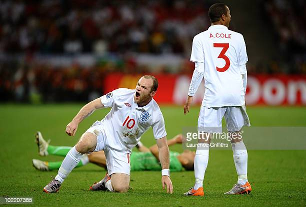 Wayne Rooney of England reacts after he tackles Karim Matmour of Algeria as Ashley Cole looks on during the 2010 FIFA World Cup South Africa Group C...