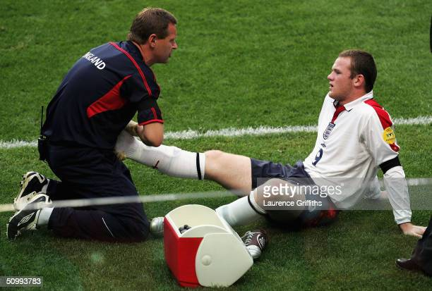 Wayne Rooney of England recieves treatment after injuring his ankle during the opening goal with David Beckham during the UEFA Euro 2004 Quarter...