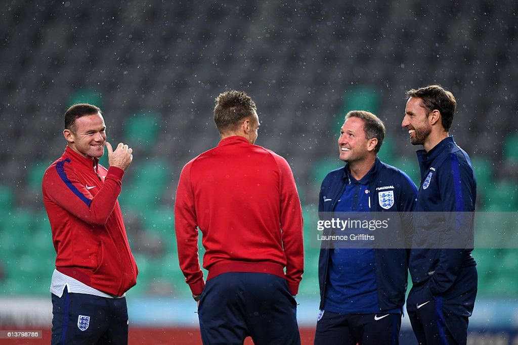Wayne Rooney of England smiles as he speaks with Interim Manager Gareth Southgate, first-team coach Steve Holland and Jamie Vardy during a tour of the stadium before an England press conference ahead of the FIFA 2018 World Cup Qualifier Group F match between Slovenia and England at Stadion Stozice on October 10, 2016 in Ljubljana, Slovenia.