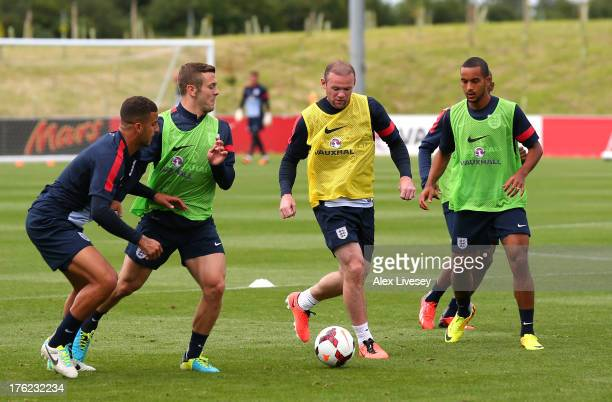 Wayne Rooney of England takes on Jack Wilshere Kyle Walker and Theo Walcott during a training session at St Georges Park on August 12 2013 in...