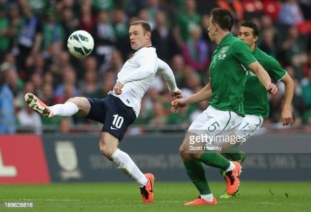 Wayne Rooney of England takes on Sean St Ledger and Stephen Kelly of the Republic of Ireland during the International Friendly match between England...