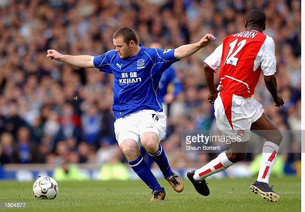 Wayne Rooney of Everton holds off Lauren of Arsenal during the FA Barclaycard Premiership match between Everton and Arsenal at Goodison Park in...
