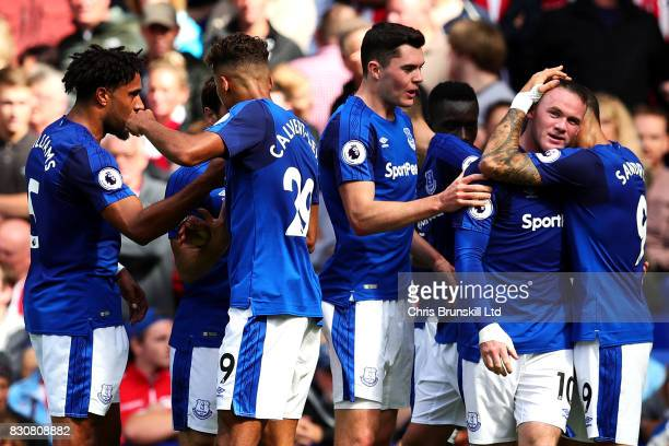Wayne Rooney of Everton is congratulated by his teammates after scoring the opening goal during the Premier League match between Everton and Stoke...