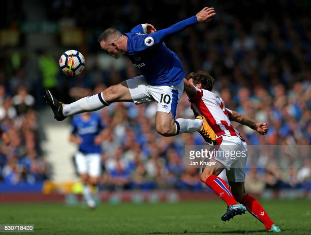 Wayne Rooney of Everton jumps to control the ball under pressure from Joe Allen of Stoke City during the Premier League match between Everton and...