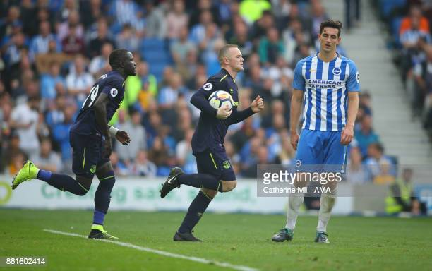 Wayne Rooney of Everton runs past a dejected Lewis Dunk of Brighton and Hove Albion back to the centre with the ball after he scores a penalty goal...