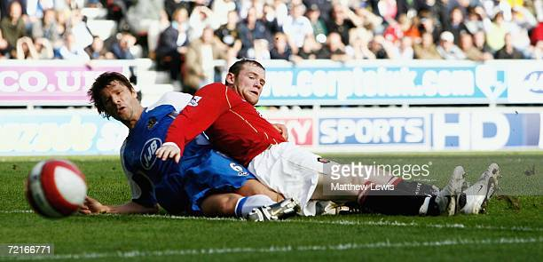 Wayne Rooney of Manchester is tackled by Arjan De Zeeuw of Wigan during the Barclays Premiership match between Wigan Athletic and Manchester United...