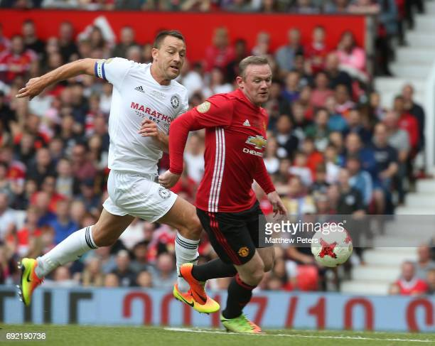 Wayne Rooney of Manchester United '08 XI in action with John Terry of Michael Carrick AllStars during the Michael Carrick Testimonial match between...