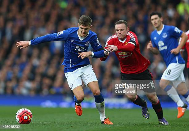 Wayne Rooney of Manchester United and John Stones of Everton compete for the ball during the Barclays Premier League match between Everton and...