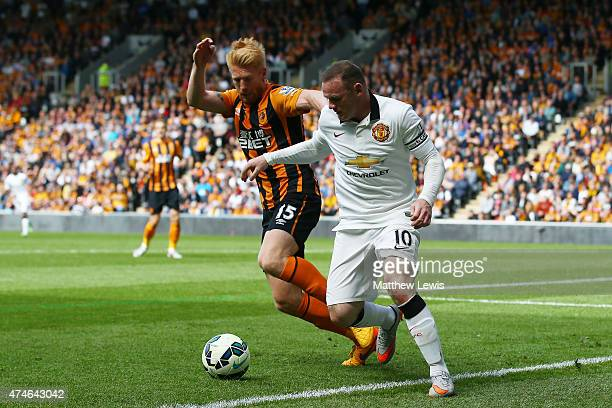 Wayne Rooney of Manchester United and Paul McShane of Hull City compete for the ball during the Barclays Premier League match between Hull City and...