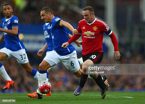 Wayne Rooney of Manchester United and Phil Jagielka of Everton compete for the ball during the Barclays Premier League match between Everton and...