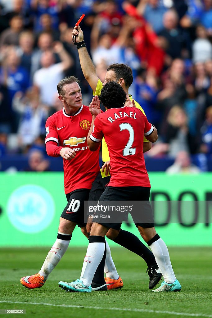 Wayne Rooney of Manchester United and Rafael of Manchester United protest as Referee Mark Clattenburg shows the red card to Tyler Blackett of Manchester United during the Barclays Premier League match between Leicester City and Manchester United at The King Power Stadium on September 21, 2014 in Leicester, England.