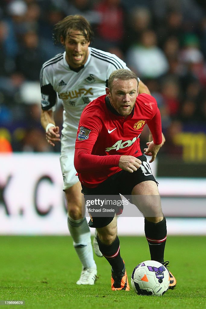 <a gi-track='captionPersonalityLinkClicked' href=/galleries/search?phrase=Wayne+Rooney&family=editorial&specificpeople=157598 ng-click='$event.stopPropagation()'>Wayne Rooney</a> of Manchester United breaks away from Michu of Swansea City during the Barclays Premier League match between Swansea City and Manchester United at the Liberty Stadium on August 17, 2013 in Swansea, Wales.