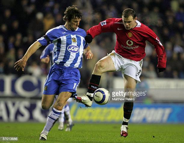 Wayne Rooney of Manchester United clashes with Arjan De Zeeuw of Wigan Athletic during the Barclays Premiership match between Wigan Athletic and...