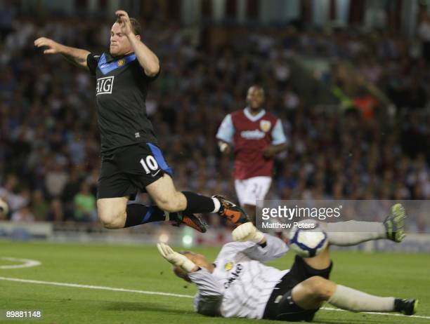 Wayne Rooney of Manchester United clashes with Brian Jensen of Burnley during the FA Barclays Premier League match between Burnley and Manchester...
