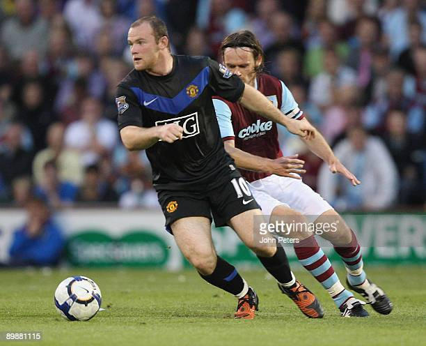 Wayne Rooney of Manchester United clashes with Graham Alexander of Burnley during the FA Barclays Premier League match between Burnley and Manchester...