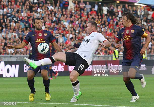 Wayne Rooney of Manchester United clashes with Javier Mascherano and Carles Puyol of Barcelona during the preseason friendly match between Manchester...