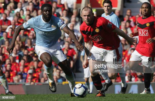 Wayne Rooney of Manchester United clashes with Kolo Toure of Manchester City during the FA Barclays Premier League match between Manchester United...