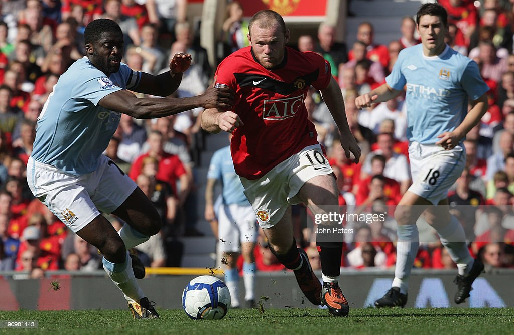 Wayne Rooney of Manchester United clashes with Kolo Toure of Manchester City during the FA Barclays Premier League match between Manchester United and Manchester City at Old Trafford on September 20 2009 in Manchester, England.