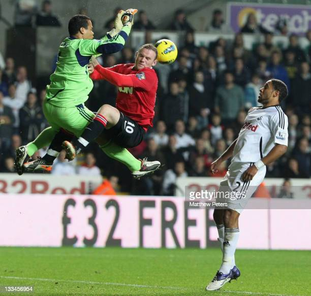 Wayne Rooney of Manchester United clashes with Michel Vorm of Swansea City during the Barclays Premier League match between Swansea City and...