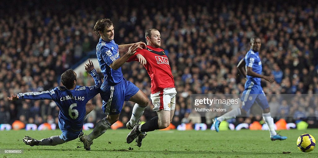 Wayne Rooney of Manchester United clashes with Ricardo Carvalho and Branislav Ivanovic of Chelsea during the FA Barclays Premier League match between Chelsea and Manchester United at Stamford Bridge on November 8 2009 in London, England.