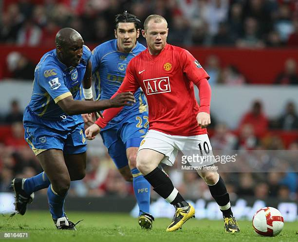 Wayne Rooney of Manchester United clashes with Sol Campbell of Portsmouth during the Barclays Premier League match between Manchester United and...