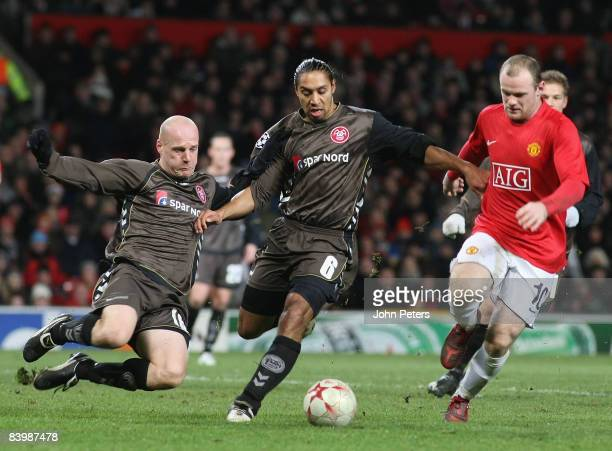 Wayne Rooney of Manchester United competes for the ball with Kasper Bogelund and Steve Olfers of Aalborg during the UEFA Champions League Group E...