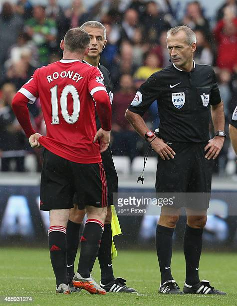 Wayne Rooney of Manchester United complains to referee Martin Atkinson during the Barclays Premier League match between Swansea City and Manchester...