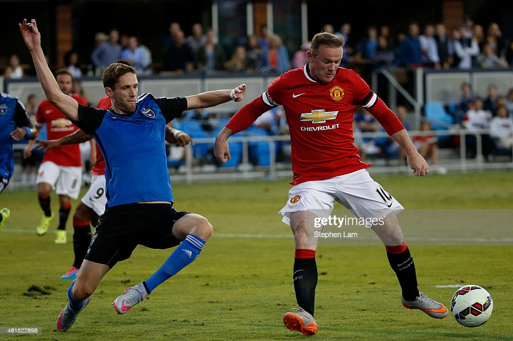 Wayne Rooney of Manchester United drives the ball as Clarence Goodson of San Jose Earthquakes defends during the first half of their International...