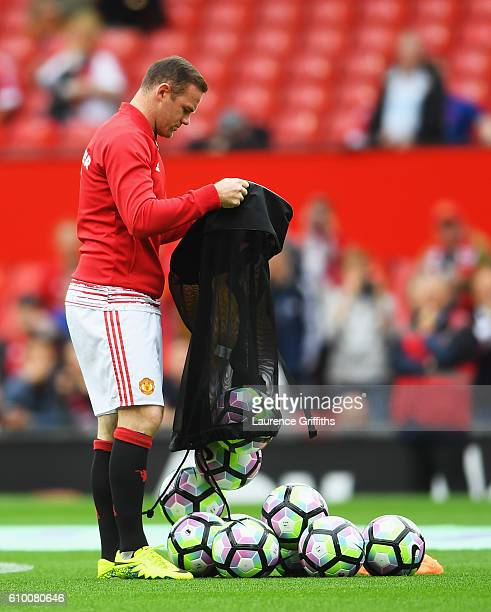 Wayne Rooney of Manchester United empty's the preimer leauge balls onto the pitch during the Premier League match between Manchester United and...