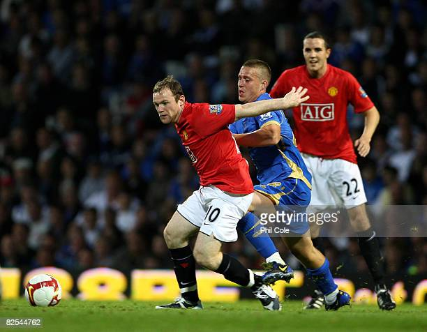 Wayne Rooney of Manchester United gets tackled by Seran Davis of Portsmouth during the Barclays Premier League match between Portsmouth and...