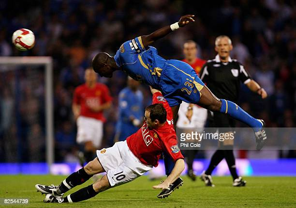 Wayne Rooney of Manchester United gets tackled by Sol Cambell of Portsmouth during the Barclays Premier League match between Portsmouth and...