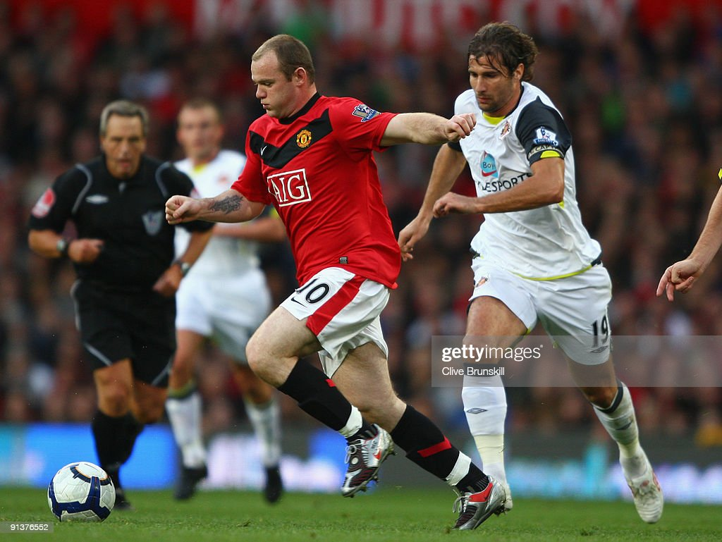 <a gi-track='captionPersonalityLinkClicked' href=/galleries/search?phrase=Wayne+Rooney&family=editorial&specificpeople=157598 ng-click='$event.stopPropagation()'>Wayne Rooney</a> of Manchester United goes past <a gi-track='captionPersonalityLinkClicked' href=/galleries/search?phrase=Lorik+Cana&family=editorial&specificpeople=662499 ng-click='$event.stopPropagation()'>Lorik Cana</a> of Sunderland during the Barclays Premier League match between Manchester United and Sunderland at Old Trafford on October 3, 2009 in Manchester, England.