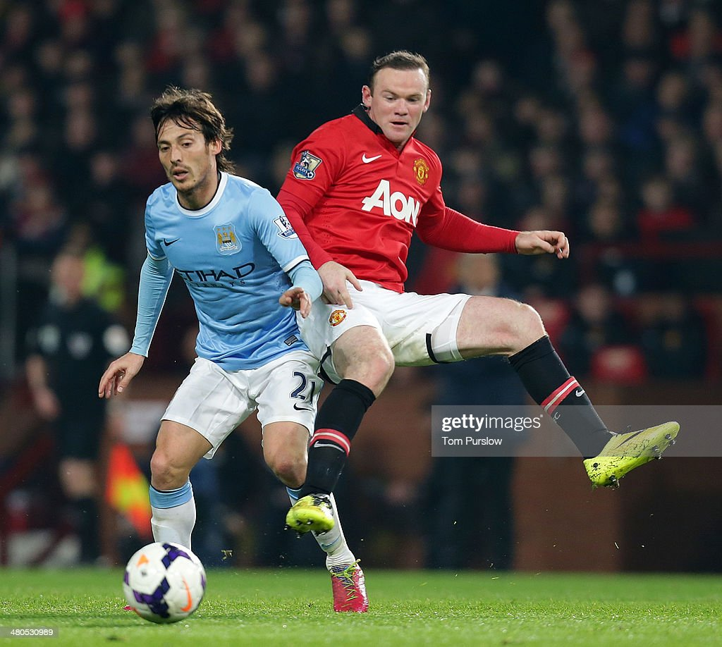 Wayne Rooney of Manchester United in action with David Silva of Manchester City during the Barclays Premier League match between Manchester United and Manchester City at Old Trafford on March 25, 2014 in Manchester, England.