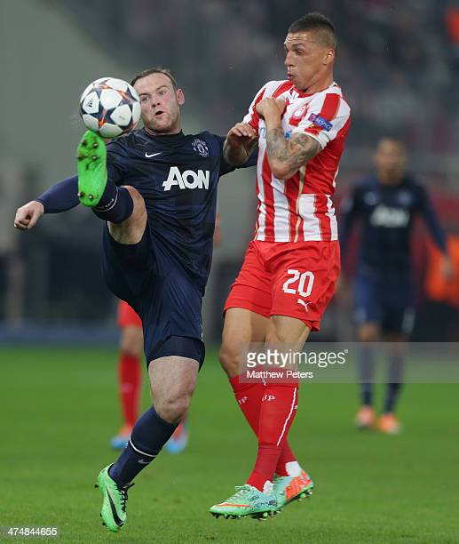 Wayne Rooney of Manchester United in action with Hernan Perez of Olympiacos FC during the UEFA Champions League Round of 16 match between Olympiacos...
