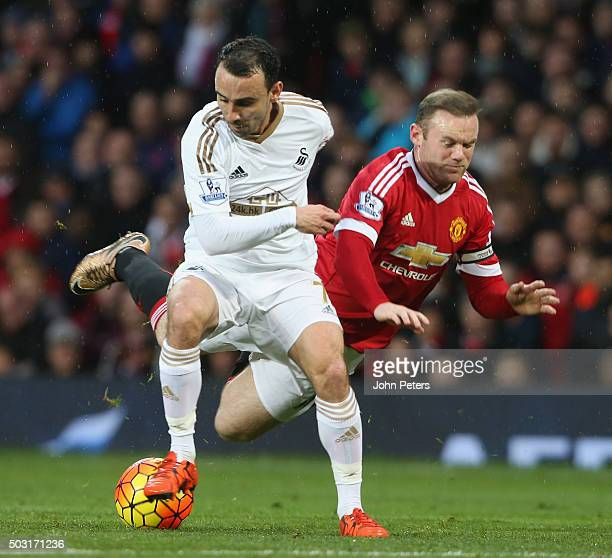 Wayne Rooney of Manchester United in action with Leon Britton of Swansea City during the Barclays Premier League match between Manchester United and...