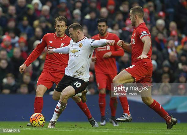 Wayne Rooney of Manchester United in action with Lucas and Jordan Henderson of Liverpool during the Barclays Premier League match between Liverpool...