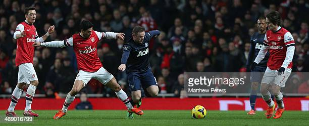 Wayne Rooney of Manchester United in action with Mesut Oezil Mikel Arteta and Tomas Rosicky of Arsenal during the Barclays Premier League match...