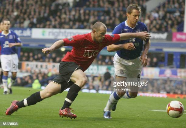 Wayne Rooney of Manchester United in action with Phil Jagielka of Everton during the Barclays Premier League match between Everton and Manchester...