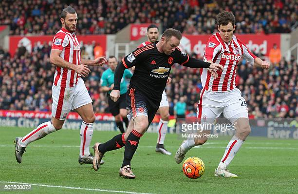 Wayne Rooney of Manchester United in action with Philipp Wollscheid of Stoke City during the Barclays Premier League match between Stoke City and...
