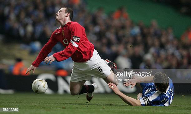 Wayne Rooney of Manchester United is brought down by Arjan De Zeeuw of Wigan Athletic during the Carling Cup Final match between Manchester United...