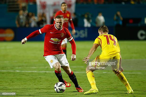 Wayne Rooney of Manchester United is challenged by Jordan Henderson of Liverpool in the Guinness International Champions Cup 2014 Final at Sun Life...